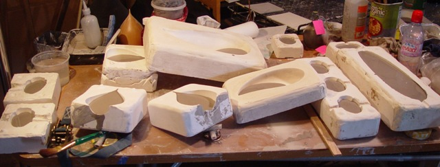"Casting ""shells"" for pit firing. After sitting for a while, the plaster absorbs water from the slip. The longer it sits, the thicker the piece. The excess slip is then poured into a bucket. After some handwork to clean and smooth the pieces, they are left to dry and then fired in an electric kiln. This will prevent breaking during the eventual pit firing."