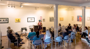 exhibition of artwork with an audience looking on during an artist's talk