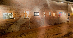 image of brick wall with row of hung artworks
