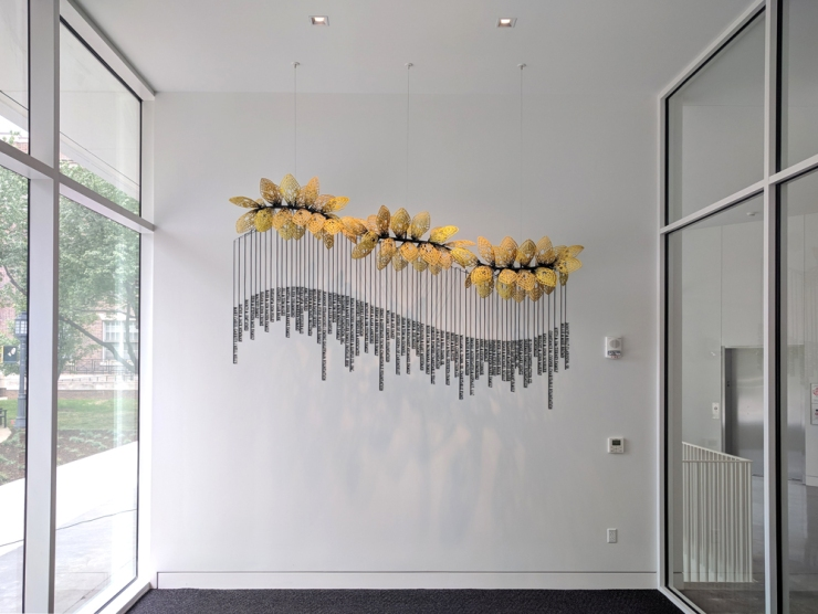 suspended and wall-mounted sculpture in glass foyer