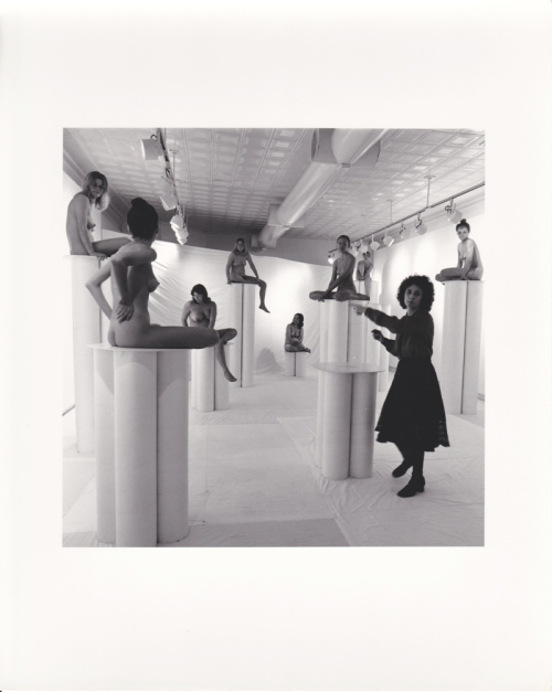 Installation view of 1976 show Women in Glasses showing artist Cyncha Jeansonne (then known as Cyndi Ketchum) with nude models on pedestals with eye glasses.