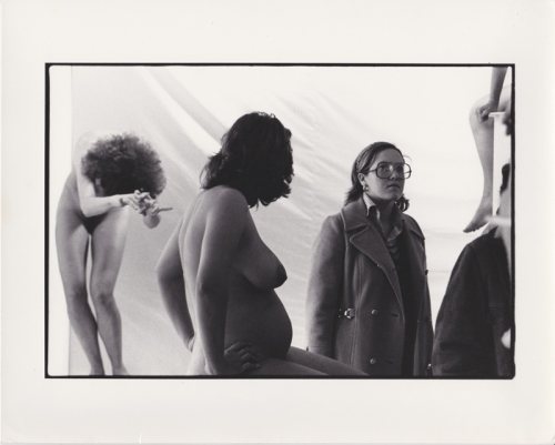 Detail view of Women in Glasses art exhibition showing a viewer looking past nude pregnant model and another posing model in the background.