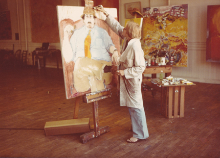 image of a woman standing and painting a large portrait on canvas