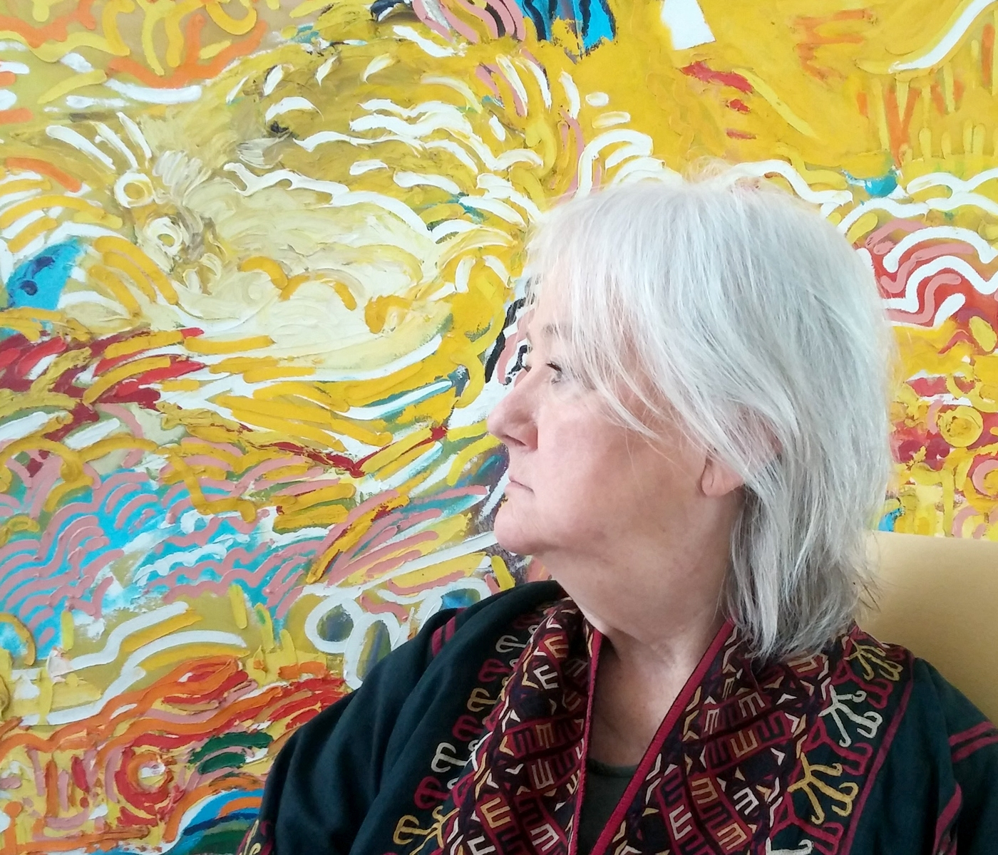 side profile of a seated woman with an abstract painting of swirling lines in the background