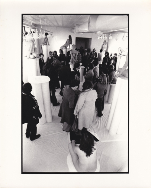 Installation view of 1976 show Women in Glasses: audience meandering around nude women on pedestals with eye glasses.